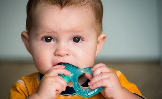 Child chewing on teething ring