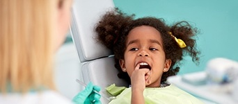 Child pointing to her tooth
