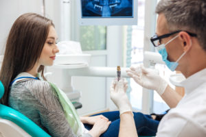 Dentist showing female patient dental implant post