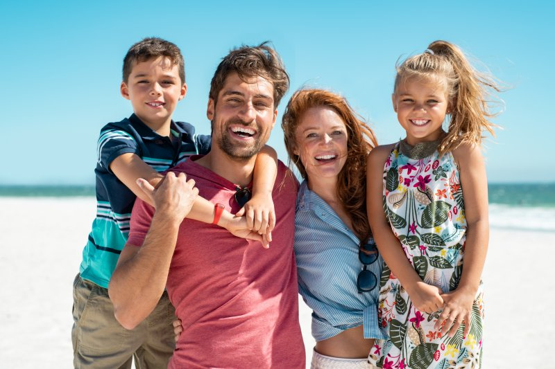 family smiling on beach during summer vacation