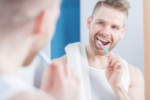 man smiling while brushing teeth