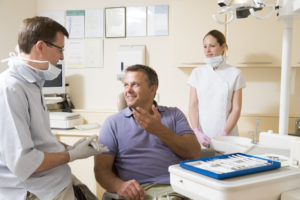 Man talking to dentist about tooth replacement