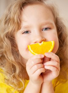 Girl smiling with orange slice