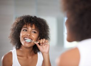 Woman brushing teeth using a high quality toothbrush