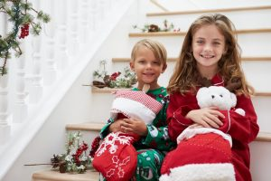 A boy and a girl sitting on a staircase smiling and holding Christmas stockings