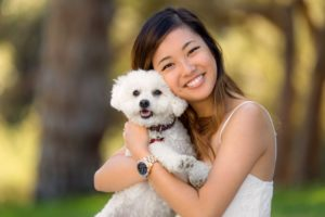 woman smiling holding white dog